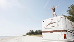 Woman standing on RV who needs RV camping tips
