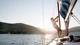 man hoisting sail on boat