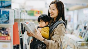 mother reading book to baby in book store