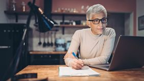 Mature woman checks for mutual fund capital gains distributions in her portfolio