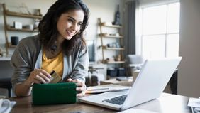Woman on computer getting the most of her travel miles and points