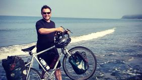 Man and bike on a beach after he quit his job to travel full-time