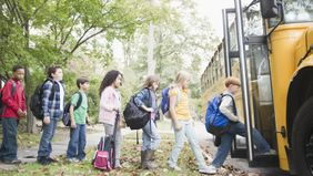 Kids getting on a bus as they head back to school.