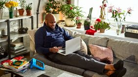 man using laptop with feet up on sofa