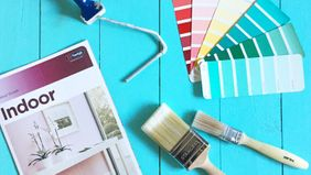 Indoor colour guide, paint brushes, and paint swatches for home renovation