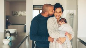 new parents and baby in kitchen