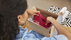 Woman opening up package of clothes.