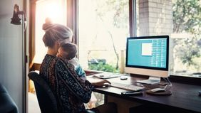 Mom working at home while holding a child.