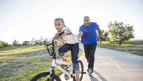 Dad teaching his daughter to ride a bike.