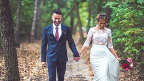 bride and groom walking in park with fall foliage in the background