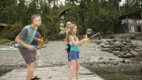 Family blowing bubbles on the dock at a vacation home shared with other families.