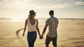 couple walking on beach talking about finances