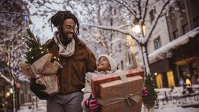 A young father and daughter carrying Christmas gifts and decorations
