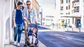 parents pushing toddler in stroller along sidewalk