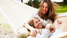 mother and daughter relaxing in hammock on vacation