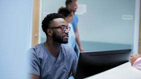 Doctor working at a computer and researching disability insurance for physicians.