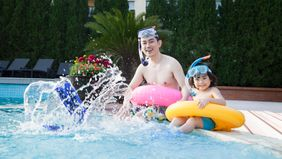 father and son wearing swim gear sitting on edge of pool
