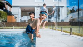 Young boys enjoying pool in the back yard.