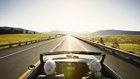 A retired couple driving a convertible on the highway