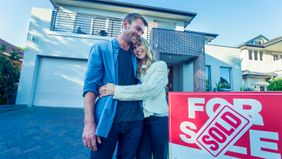 Couple standing in front of a home with for-sale sign.
