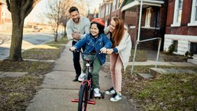 Mom and dad pushing child on a bike, pondering who should be the trustee and guardian for their child.