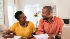 A couple discusses guaranteed universal life insurance at the dinner table