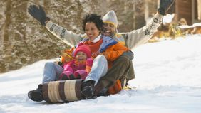 Family sledding together on a winter getaway.
