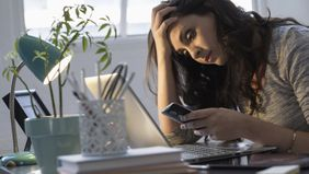 Woman looking at her phone trying to research her debt collection rights.