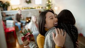 Friends hugging in new holiday tradition that helps save money.