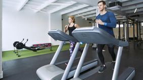 Man and woman running on treadmills in a gym