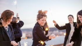 A group of friends waving around sparklers.