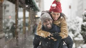 Man giving woman a piggyback ride in snowy weather