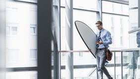 Executive with his surfboard at the office as he navigates his unlimited PTO policy