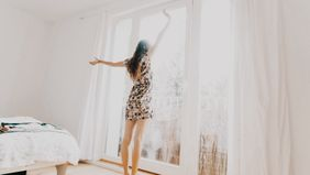 Woman standing on her bed looking out the window