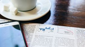 Coffee, smartphone and financial newspaper on a table