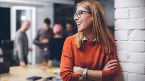 Happy woman at work thinking about career goals.