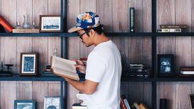 man reading in front of bookshelf