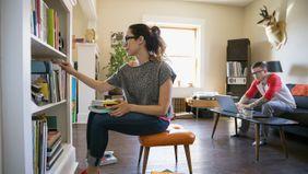 woman tidying bookshelves in living room