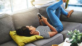 woman laying on couch and scrolling through social media