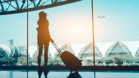 woman looking out airport window at departing plane