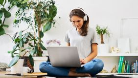 woman wearing headphones working on laptop
