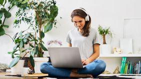 woman wearing headphones working on laptop