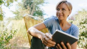 Woman sitting outdoors using a tablet