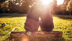 Two women sitting on a log in sunlight.