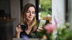 Woman drinking coffee and reading Northwestern Mutual Market Commentary.