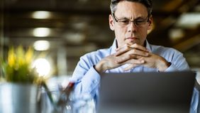 Man reading Northwestern Mutual Market Commentary on his computer