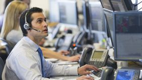 a man working at a trading desk at a financial firm