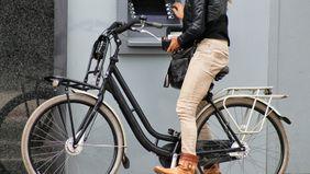 woman on bike using atm