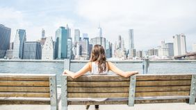 woman on bench looking at nyc skyline