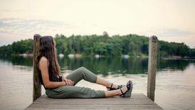 woman sitting on dock looking at lake